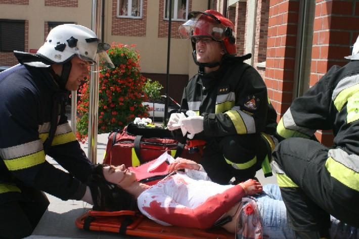 Osoba w ciężkim stanie chwilę po wyniesieniu z budynku.
